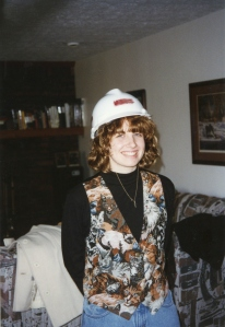 A picture of me in a hardhat from my first employer. Ignore the mom jeans and cat vest. It was 1996
